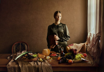 Woman wearing green clothing with still life of food and drink