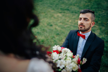 Stylish bearded groom in a tuxedo with a red butterfly and suspenders with his bride with long black hair in a pink long dress is holding a bouquet of peonies with a tied ribbon walking in green park