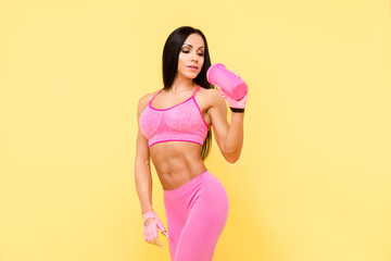 Muscular brunette woman in pink leggings, top and gloves drinking from the pink bottle. Isolate.