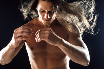 muscular man with long hair, clasps hands in fist, black background