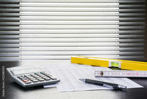 kugelschreiber tabellen taschenrechner zollstock und wasserwaage auf schreibtisch vor. Black Bedroom Furniture Sets. Home Design Ideas