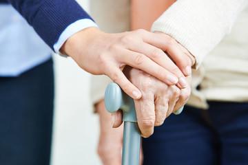 Hand holding hand of senior woman