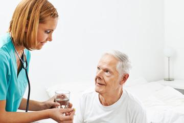 Old man getting medicine from nurse