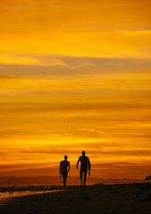 Surfing couple walking at sunset, Rincon, Santa Barbara, California, United States of America