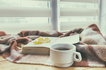 Cup of coffee and book with autumn yellow leaf surrounded wool blanket on windowsill