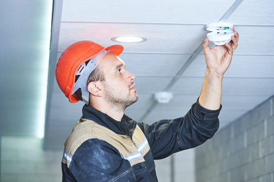 worker installing smoke detector on the ceiling