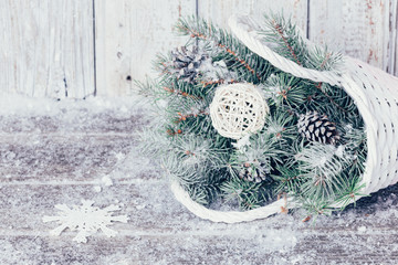 Composition with Christmas decorations in basket, fir tree on wooden background