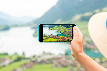 Photographing with phone beautiful landscape with lake and village in Switzerland