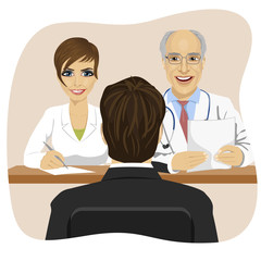 man sitting opposite mature doctor with assistant sitting at a office desk