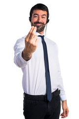 Young man with a headset coming gesture