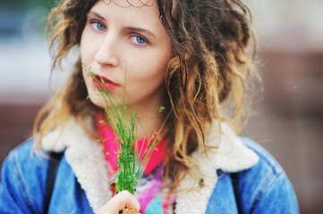 Young cute girl with dreadlocks with a bunch of grass on the str