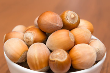 Nuts in a white plate on a wooden table. Hazelnuts