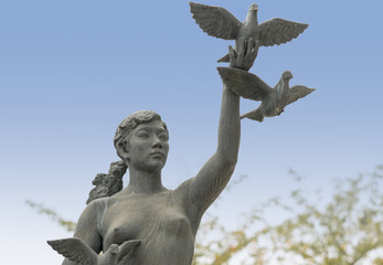 Kyoto, Japan - September 15, 2016: Gray peace statue of girl releasing three doves against blue sky. Statue at the bridge on Nijo Dori over the canal.