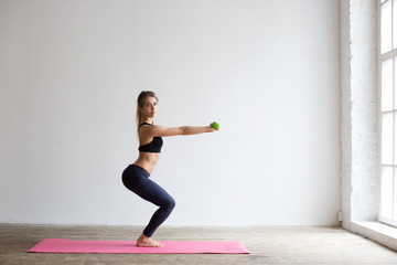Portrait of young woman in sportswear, doing fitness exercise.