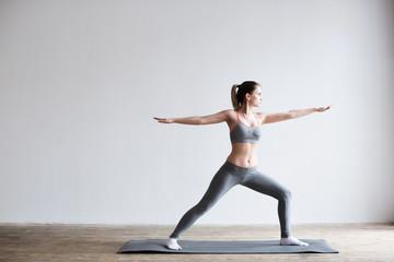 Woman doing yoga indoors on yoga mat. Fototapete