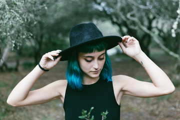 Pretty girl with short dyed hair toughing her hat.