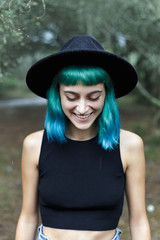 Smiling pretty girl in black hat and crop top.