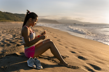 Swarthy girl using her devices on the beach.