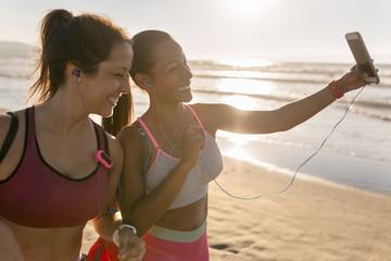 Two fit sportswomen making a selfie on the beach.