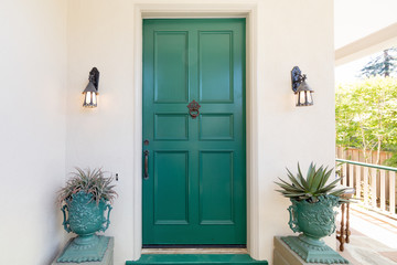 Green entry door with door knock.