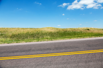 A road cutting through grasslands in southern South Dakota on a summer day.