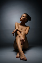 Studio photo of beautiful naked woman sitting