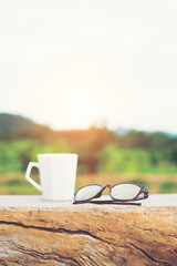 White of hot coffee cup with glasses on the bench with green nat