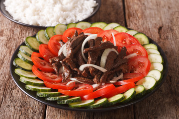 marinated roast beef Lok Lak with vegetables and a side dish of rice close-up. horizontal