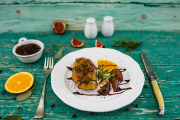 Roasted breast of duck with oranges and figs, rosemary and sage on wooden table.