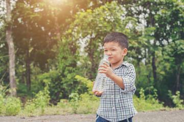 Little cute asian boy drink water on the roadside.