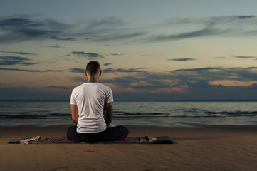 Yoga man sitting on the beach. Meditation pose