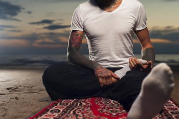 Tattoo man practicing yoga lotus pose on the beach