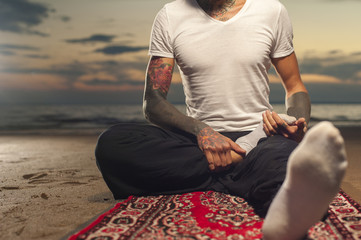 Flexible man with tattoo doing yoga lotus pose