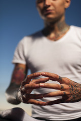 Closeup of male hands in meditation pose.