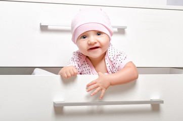 Portrait of a cheerful baby looking out of the the children's chest of drawers