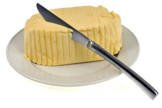 Motte de beurre dans une assiette avec un couteau