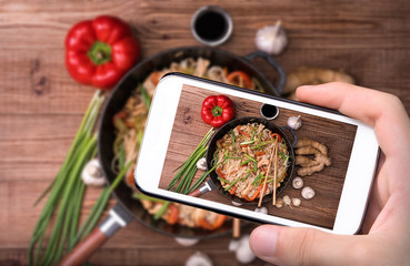 Hands taking photo spicy chicken and veggie noodles with smartphone.
