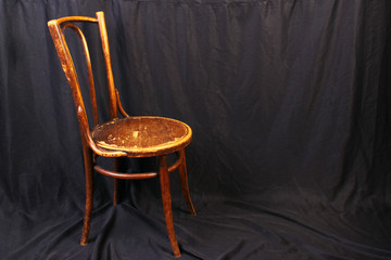 Vintage old wooden chair against black cloth background