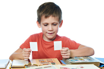 Boy with his collection of old postage stamps isolated