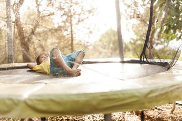 Little boy relaxing on trampoline