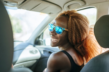 Happy young woman in a car