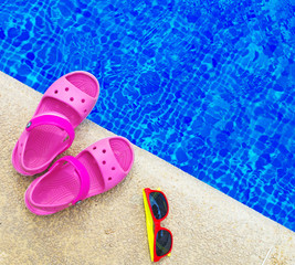 Slippers and sunglasses near the pool. Space for text.