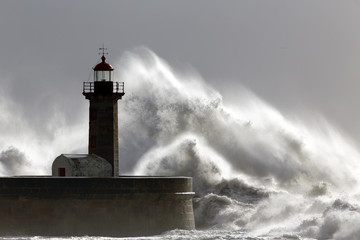 Big stormy waves over old lighthouse