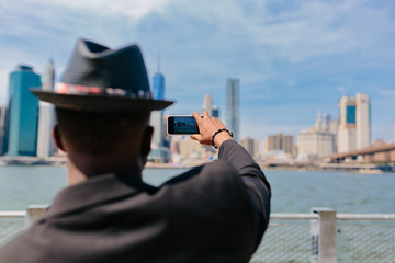 Young Fashionable Guy Taking Picture of the Manhattan Skyline . New York City