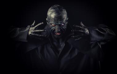Studio portrait of a man in monster makeup, dark background