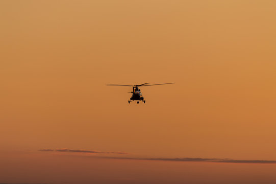 Silhouette of helicopter with sunset sky