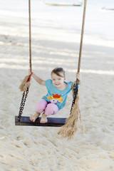 Glückliches Mädchen schaukelt am Strand