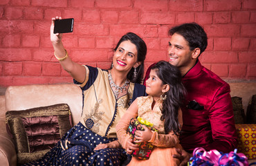 Indian family taking selfie with smartphone indoors, indian women taking selfie with husband and cute little daughter on diwali