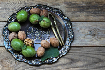 Fresh walnuts in a green shell, a vintage wooden background