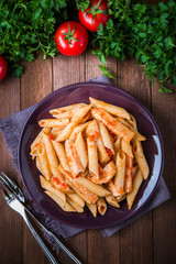 Penne pasta with chicken and tomato sauce on dark wooden background top view. Italian cuisine.